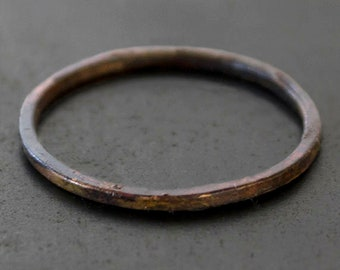 Skinny burnt 10k gold band ring with a wabi sabi organic silhouette. Hammered + oxidized gold ring. Hand crafted.