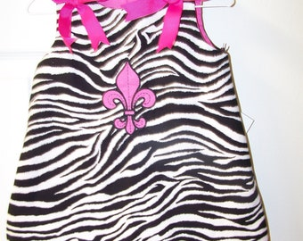 Love zebras??  This handmade dress is embroidered with a hot pink fleur de lis to set it off!
