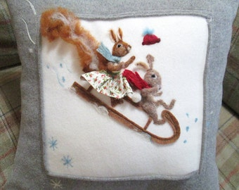 Gray winter pillow / cushion cover with needle felted squirrel and rabbit on a sledge whizzing down the snowy slope design