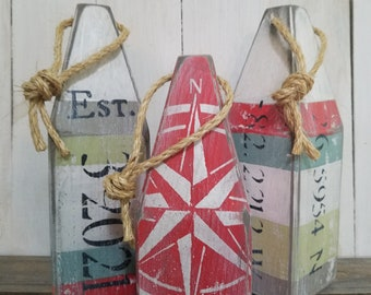 Three buoy pained buoy tabletop set - hand painted with sea glass colors - small buoy is a bold Coral Red color with Nautical compass design
