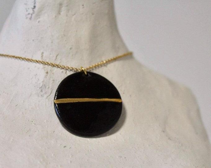 Round black gold porcelain bead on a golden necklace