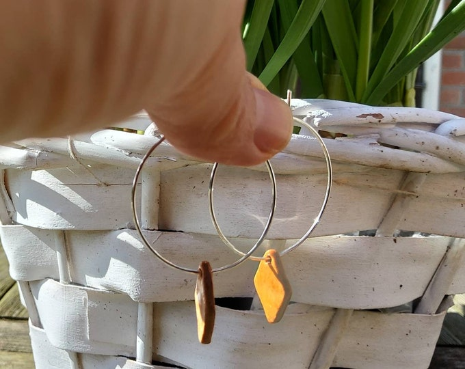 Silver creole earring with a saffron yellow rhombic handmade porcelain bead