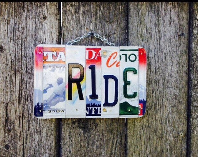 License plate art. Skier. Ride. License plate. Sign. Cabin. Ski. Snow. Mountain. Ski lodge. Skiing. Cabin decor. Sled. Sleigh
