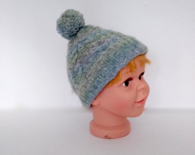 Blue alpaca pompom hat for child, handknit cable design