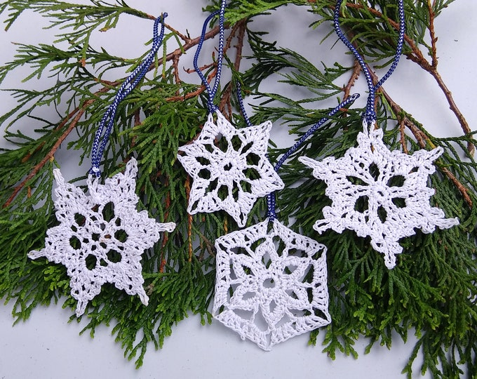 Set of 4 white crochet snowflakes with silvery accents.