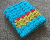 Crochet baby blanket in red, green and blue. Ideal new baby gift.