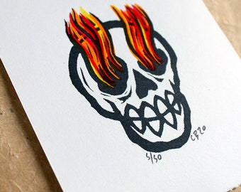 Flaming Skull. A hand carved stamp/relief print of a Flaming Skull with hand colouring in an edition of 50