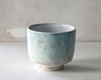 Handmade speckled white and turquoise ceramic cup with foot