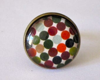 Cabochon ring in fall colors, orange, green, Brown dots. Glass and bronze.