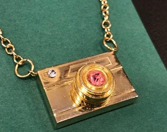 Vintage gold tone metal camera pendant necklace.