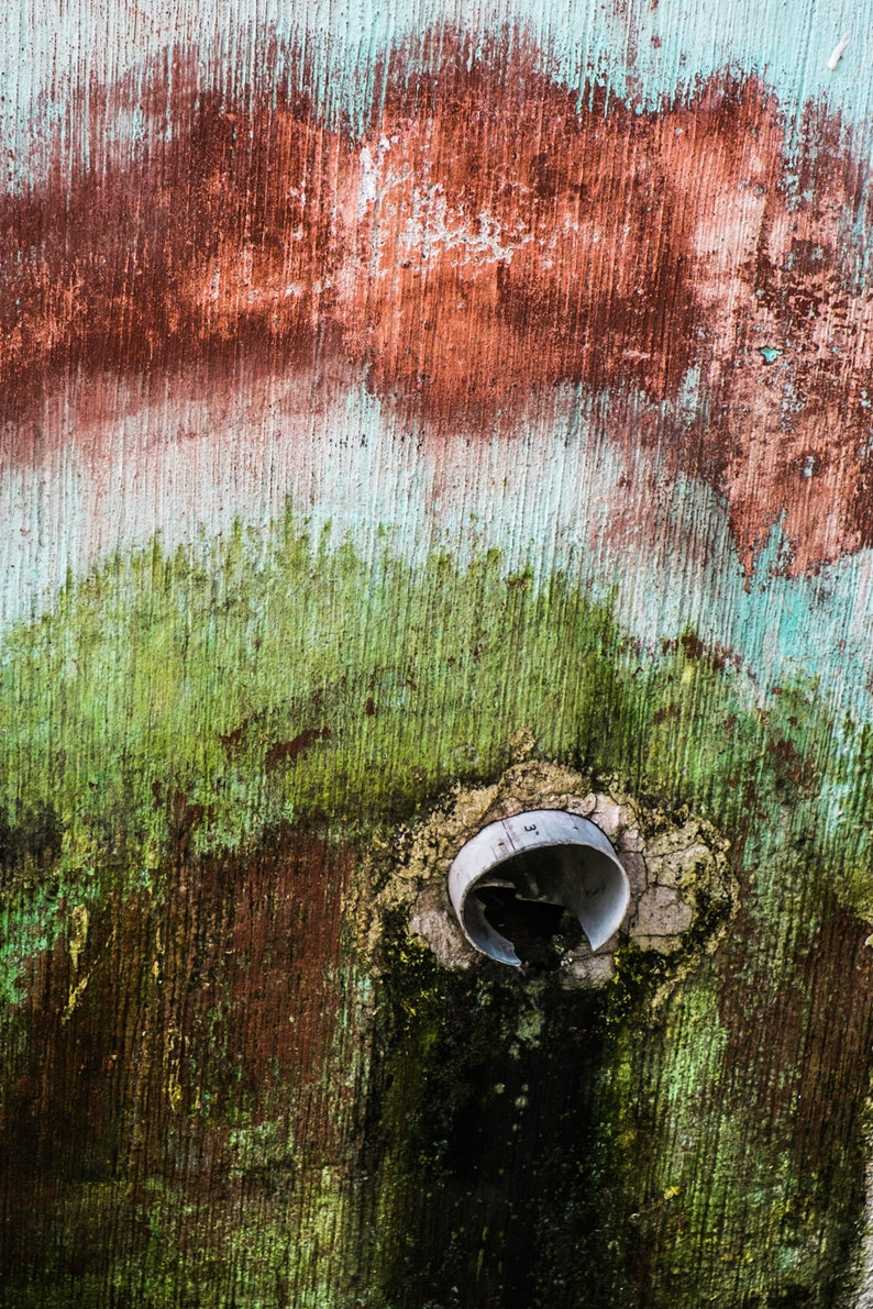 Drain pipe in red, white and green wall in Quetzaltenango, Guatemala- a  color photograph