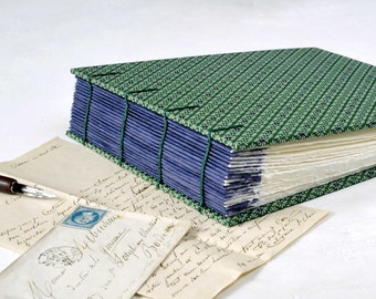 """A small handmade album for your 4x6"""" photographs. Coptic bound in dark green and purple."""