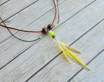 Gele parkiet veren hanger tribale halsketting bruin leren bandjes groengele glaskralen dames sieraad handgemaakte boho sieraden uniek mode
