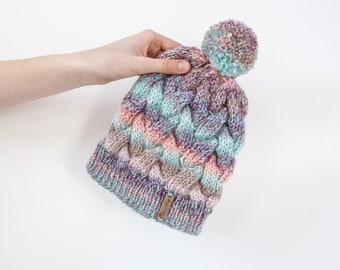 Colourful hand knitted cable pom pom hat. Women's thick chunky bobble beanie. Turquoise mix, variegated yarn, textured winter accessory.