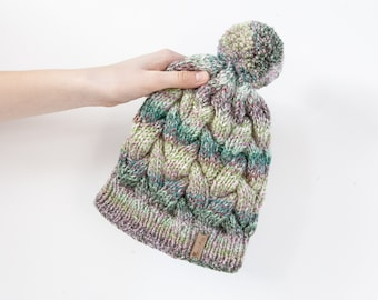 Colourful hand knitted cable pom pom hat. Women's thick chunky bobble beanie. Green mix, variegated yarn, textured winter accessory.