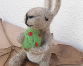 Easter Bunny, needlefelted, holding a green easteregg