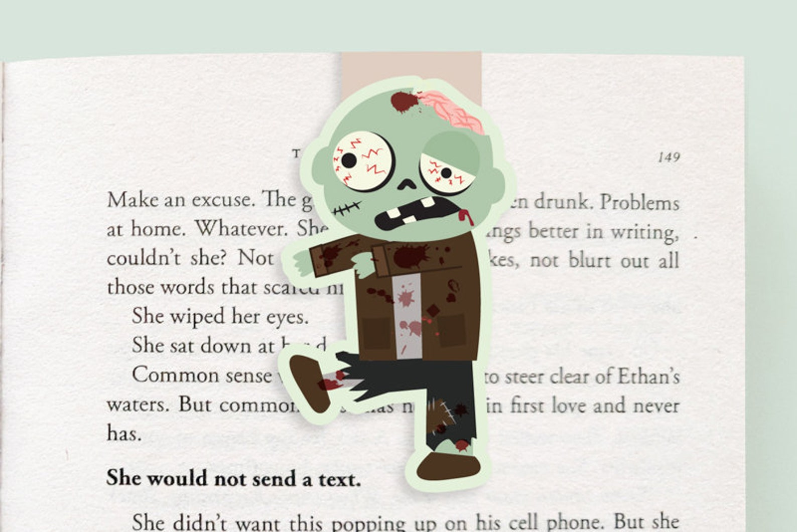 An open book with a bookmark of a green zombie walking