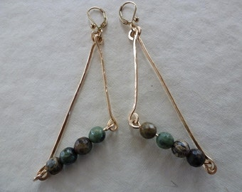 Hand forged gold sticks and green opal stones triangulate naturally as Sticks And Stones Earrings.