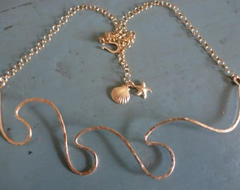 The Third Wave Necklace is a gold handshaped and hammered triple wave on gold chain to adjust from 24 inches up. Gold charms and hook.