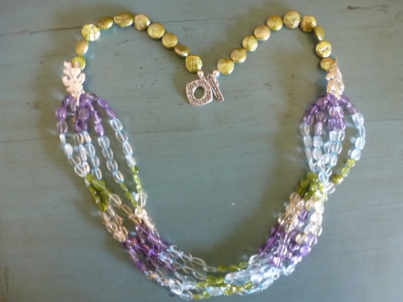 Soft Dreams Necklace is 5 strands of pastel oval gems gathered into brushed silver oak leaves and coin pearls and secured by a silver toggle