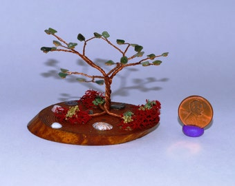 miniature wire tree with polished green stones and a wood base