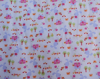 Childrens fabric with bunnies, little green trees and pink houses.