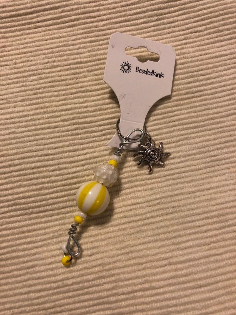 Yellow zipper pull with sun charm
