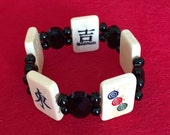 Good luck MAH JONGG tile bracelet. Carved and painted bone tiles, multi-faceted black jet oval beads and round black Czech glass beads.