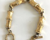 Vintage 1950s MONET gold-plated. florentined, textured, lucky bamboo link bracelet. DETAIL Bamboo-shaped toggle clasp. Monet hang tag. EUC