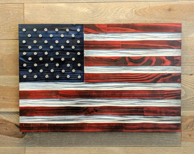 US Flag carved in wood with .40 nickel plated brass in place of the stars. Red, White and Blue colors unique chisel texture. Rustic flag.
