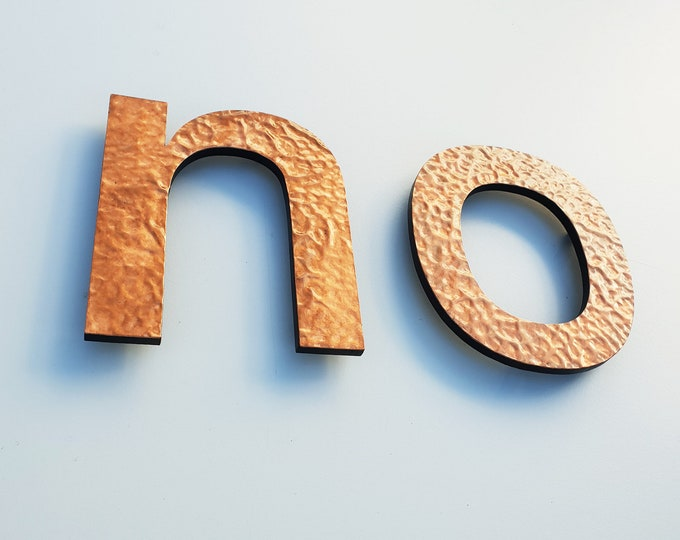 "Large modern letters floating hammered or brushed copper in lower case Antigoni  9""/225mm high - with some discreet seams d5"
