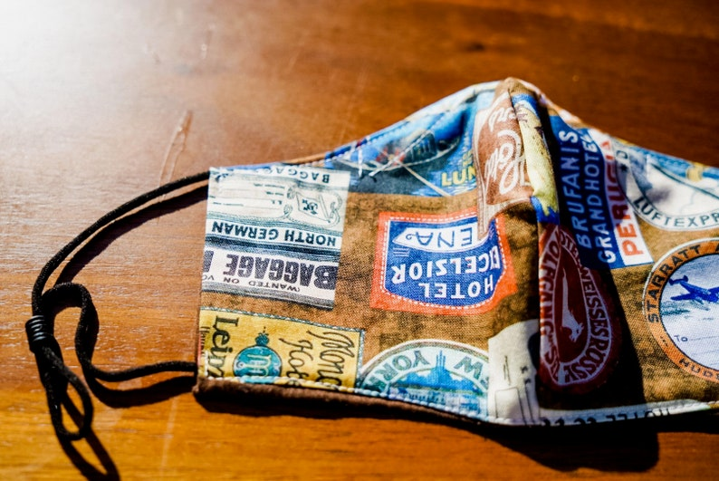 Travel Prints Reversible Cotton Mask With Filter Pocket image 7. The face mask has images of various travel-related businesses.