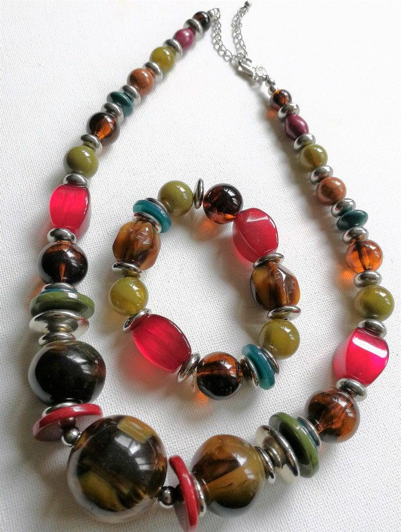 plastic beaded necklace and matching bracelet some marbled and some moon glow beads Added in April Jewellery set