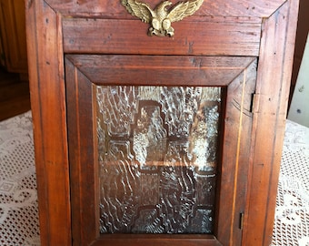 A Rustic Crusty Wood Wall Cabinet With A Plexiglass Frosted Decorative Front Window And A Metal Gold Eagle Decor With An Early American Look