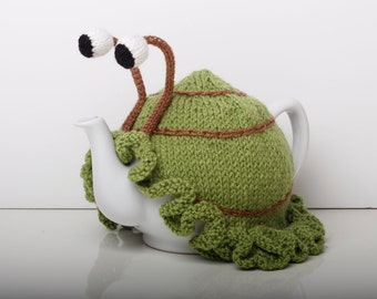 Knitted green snail tea cosy with frilly bottom. Washable fits 6 cup and 2 cup pots.