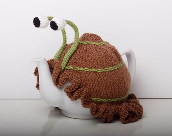 Knitted brown snail tea cosy with frilly bottom. Washable fits 1 litre teapot.