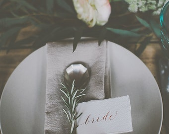 Boho style wedding place names on torn watercolour paper