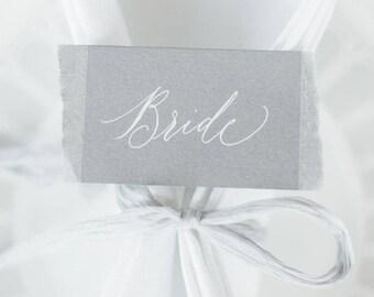Light grey torn edge calligraphy wedding place names