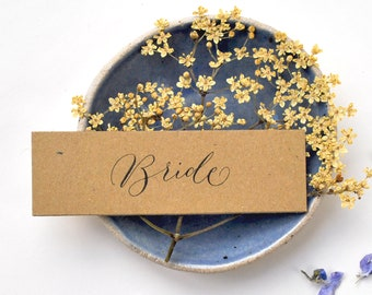 Elegant rustic wedding place names - recycled kraft card, black handwritten calligraphy