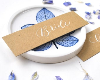 Elegant rustic wedding place names - recycled kraft card, white handwritten calligraphy