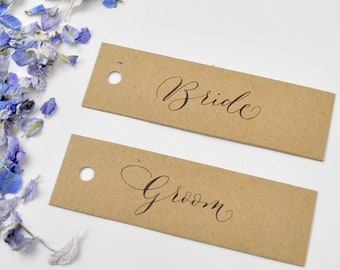 Elegant rustic wedding place names - recycled kraft card, black handwritten calligraphy, punched hole
