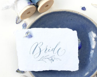 Torn edge wedding place names on luxe, nature-friendly white cotton rag paper