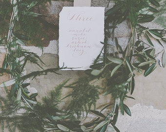 Individual table plan cards in a flowing, boho calligraphy style