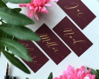Elegant calligraphy place names in gold ink on burgundy card