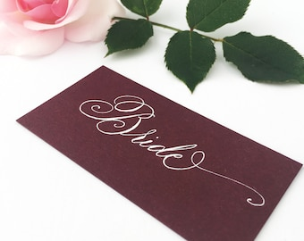 Luxury burgundy wedding place names with flourished hand calligraphy in white ink / escort cards / place cards / personalised name cards