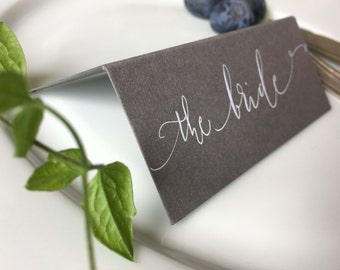 Handwritten calligraphy place names on mid-grey card