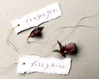 Luxe handwritten calligraphy tags with plum/burgundy lettering and gold thread