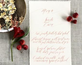 Elegant calligraphy wedding menus in coral ink on luxe torn edge paper