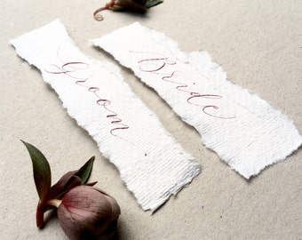 Torn, textured narrow wedding place name tags with plum/burgundy handwritten calligraphy