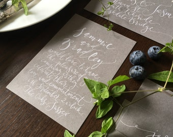 Handwritten calligraphy invitation on grey card